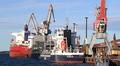 Kuva satamasta, laiturissa jonossa kolme laivaa, etualalla satamanosturi.