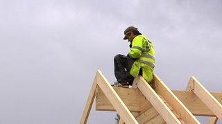 Rakentaja istuu katon harjalla.