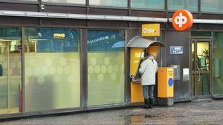 Ihminen pankkiautomaatilla.