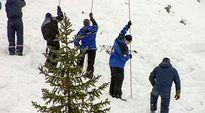 miehet mittaavat kepeillä lumen syvyyttä