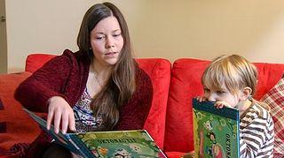 Hoitaja lukee kirjaa lapselle