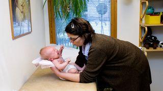 Terveydenhoitaja tutkii vauvaa.