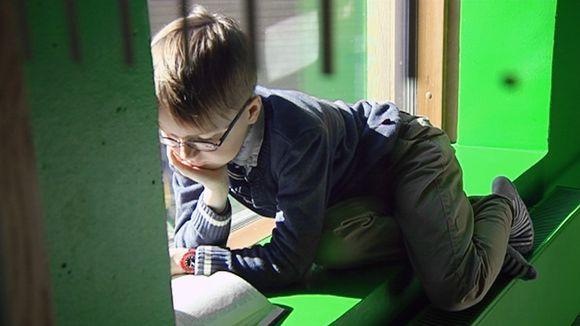 Lapsi lukee kirjaa ikkunalaudalla.