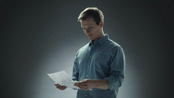 Mies lukee kirjettä.