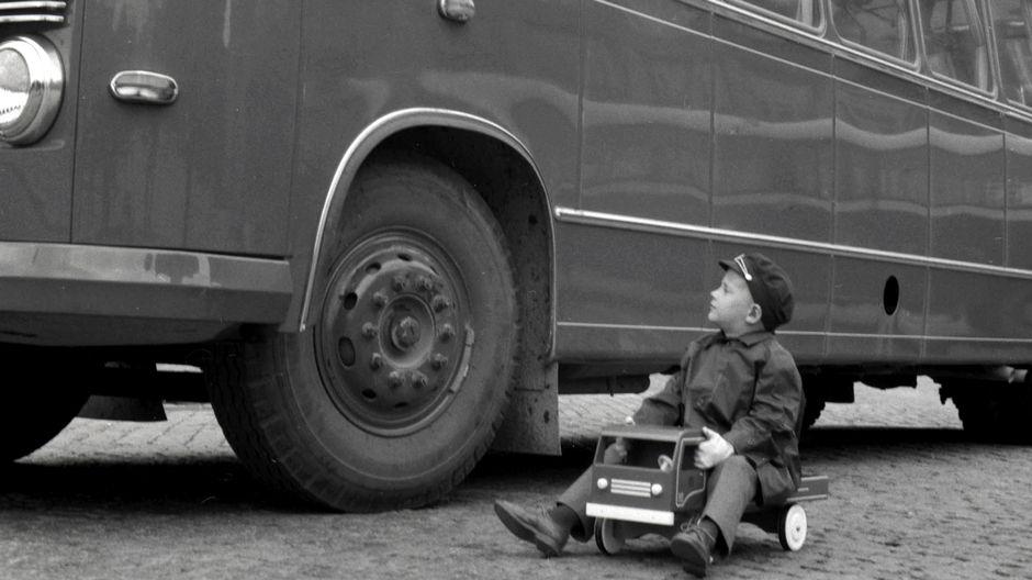 Pieni poikaa ajaa leikkiautolla linja-auton vieressä.