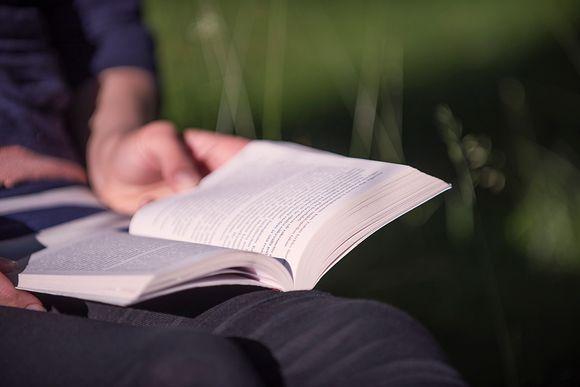 Nainen lukee pokkaria.