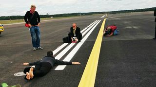 Sipoolainen lentokonebongari Heidi Lassila syleilee kiitotien pintaa.