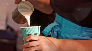 Kahvilatyöntekijä kaataa vaahdotettua maitoa pahviseen kahvinukiin.