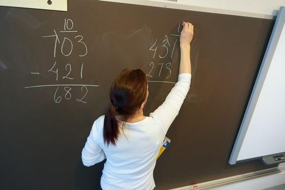 Opettaja liitutaulun äärellä.