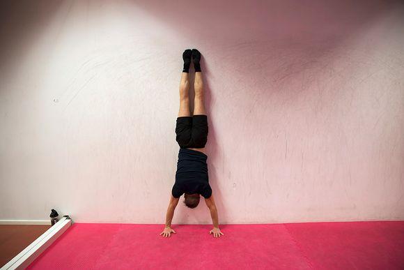 Mies harjoittelee käsilläseisontaa seinää vasten.