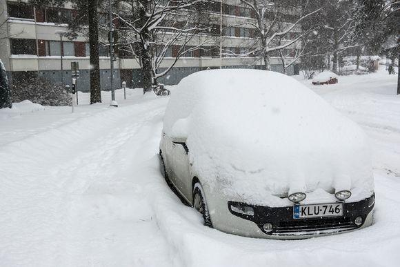 Auto parkissa lumeen hautautuneena.