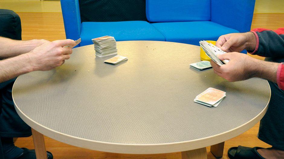 Asiakkaat pelaavat korttia ajankuluksi.