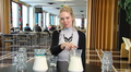 Video: nainen pöydässä, jossa kaksi kannua maitoa