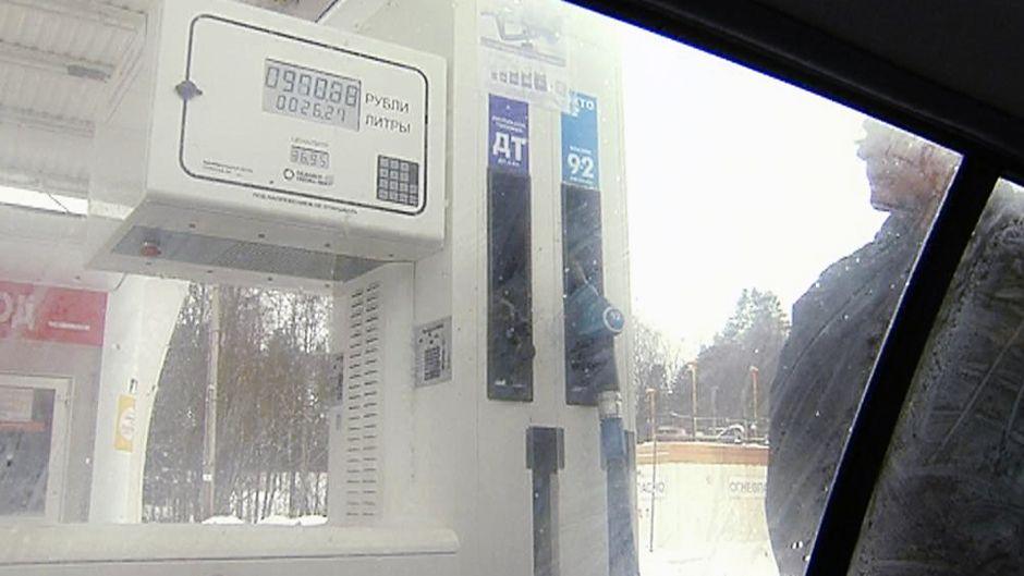 Auton ikkunan läpi kuvattu bensamittari huoltoasemalla.