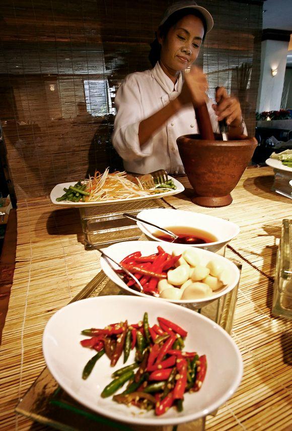 Thaimaalainen kokki valmistaa tulista Som Tam -salaattia.