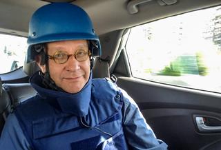 Tom Kankkonen autossa luotiliivit päällä ja kypärä päässä.