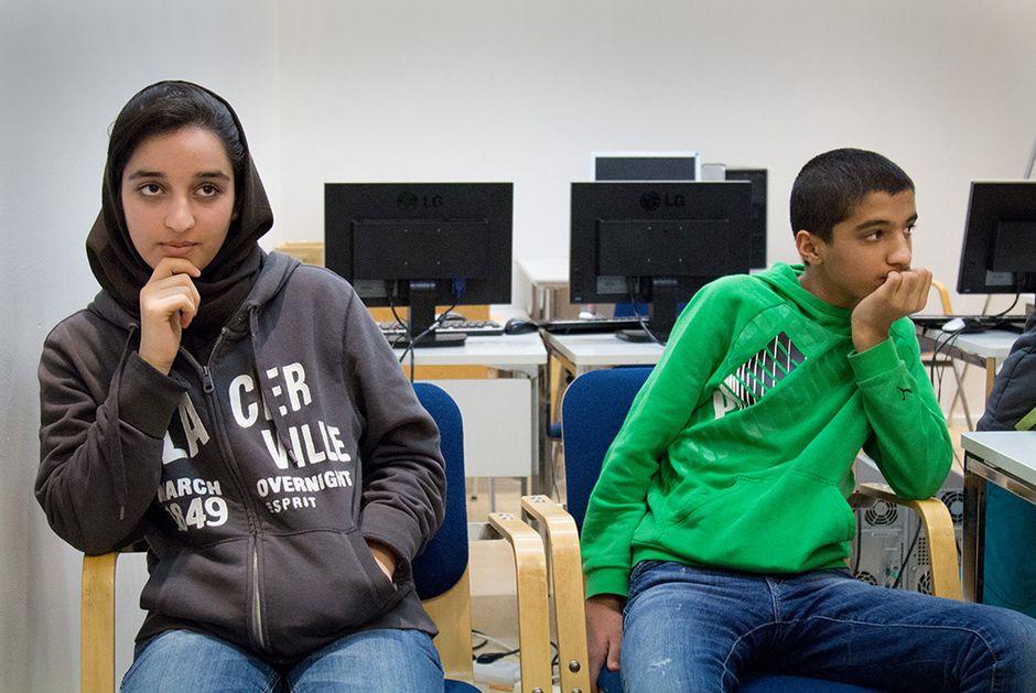 Poika ja tyttö luokassa, takana tietokoneita. Suomen kielen tunnilla. Turvapaikkaa hakevien nuorten tavoitteet ovat ammattiopinnoissa.
