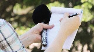 Toimittaja mikrofoni, lehtiö ja kynä kädessä.