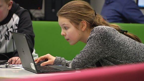 Koululainen tietokoneen ääressä.