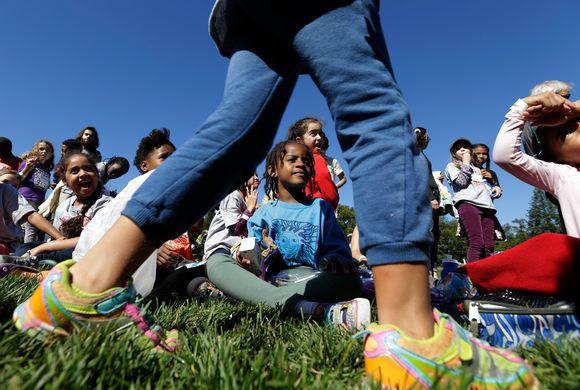 Lapsi seisoo etualalla ja lapset takana monta lasta monesta eri kulttuurista.