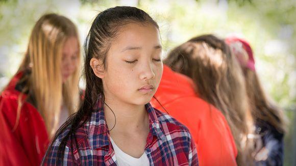 Tyttö silmät kiinni keskittyneenä.