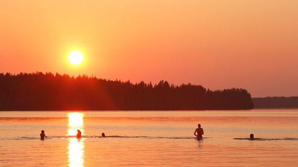 Ihmisiä uimassa järvessä auringonlaskun aikaan.