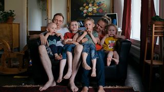 Nelilapsinen perhe istumassa ahtaalla sohvalla.