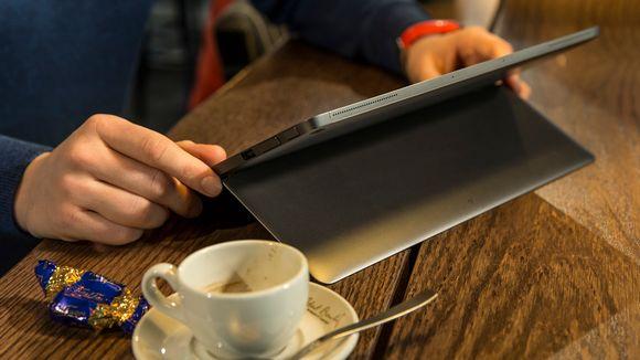 Miehen kädet tietokoneella kahvilan pöydän ääressä.