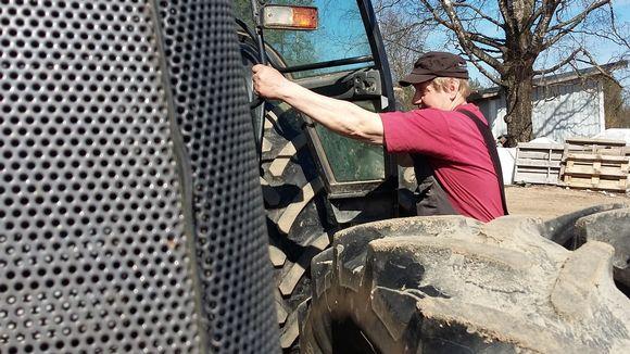 Maanviljelijä nousee traktoriin