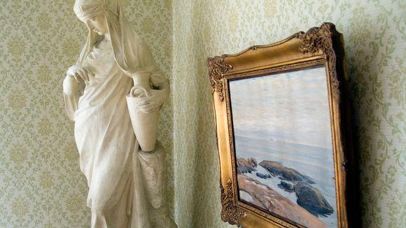 Näkymä sisältä Kotkaniemeä. Päähuoneen nurkassa on veistos ja merimaisemaa esittävä öljyvärimaalaus, joka on kullatuissa kehyksissä.