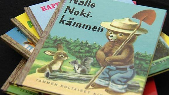 Tammen Kultaisia kirjoja pinossa.