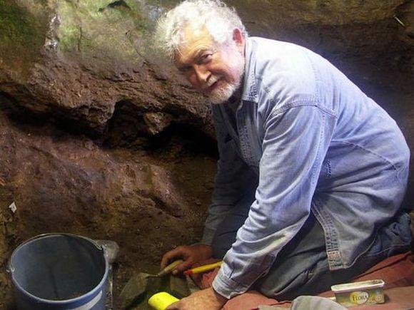 Antropologi Lawrence Straus polvillaan luolassa, kädessä ja vieressä arkeologin välineistöä.