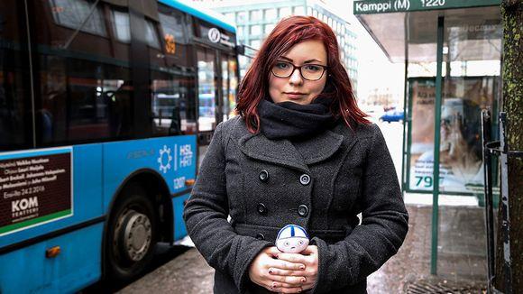 nainen busipysäkillä nukke kädessään