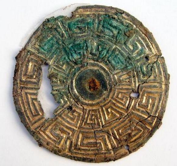 Pyöreä ornamenttikoristeinen solki, jonka kultauksen alka pilkottaa paikoin vihreää metallia.