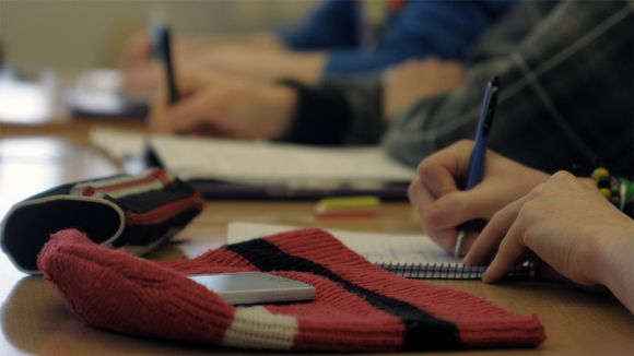 Opiskelijalla puhelin pöydällä oppitunnin aikana.