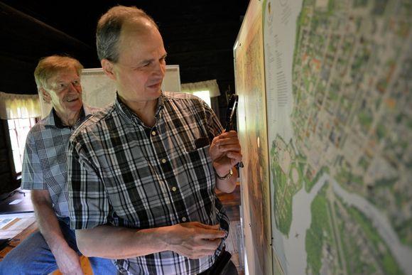 Miehet tutkivat historiallisia karttoja.