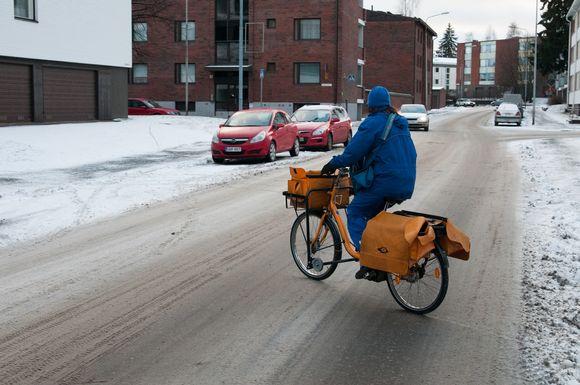 Postinjakaja ajaa pyörää Kuopiossa.