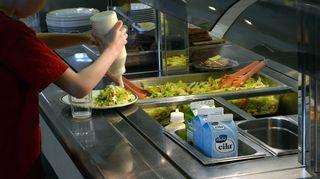 Koululainen ottaa ruokaa.
