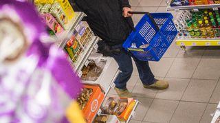 Mies ostoskori kädessä kaupassa.