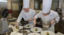 Kaksi kokkiopiskelijaa laittamassa ruokia lautasille SM-kilpailussa.