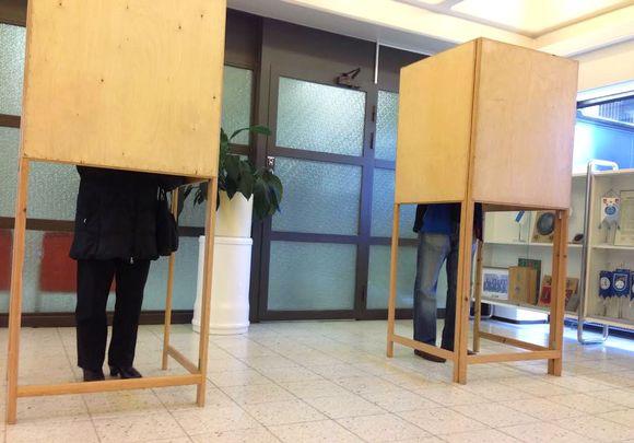 Ihmisiä äänestämässä vaalikopissa.