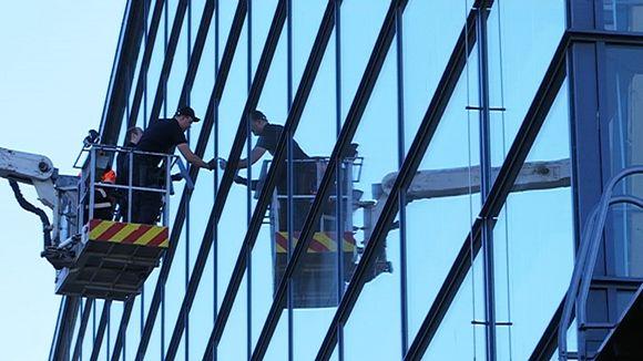 Video: Kolme miestä pesee Sibeliustalon ikkunoita nostokorista.