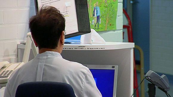 Hoitaja tietokoneen äärellä.
