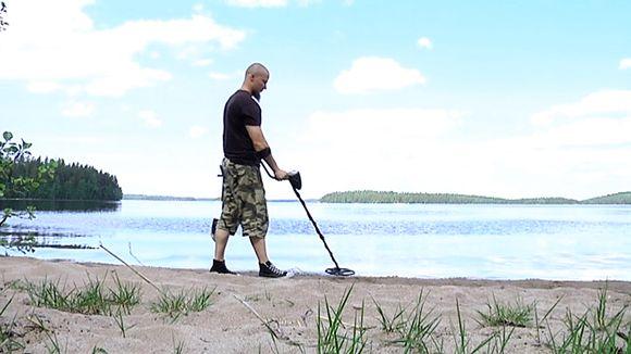 Jarkko Lehtinen haraa metallinpaljastimella rantaa.