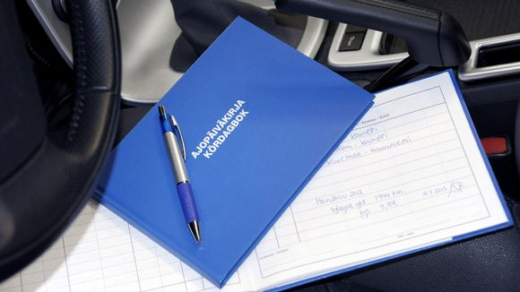 Ajopäiväkirja auton etupenkillä.