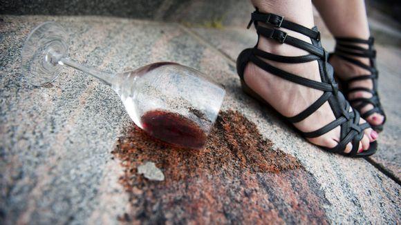 Viinilasi kaatuneena naisen jalkojen juuressa.