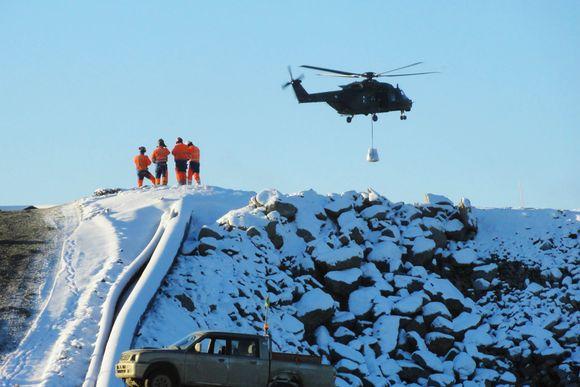 Helikopteri ja pelastushenkilöstöä kipsisakka-altaan vallin päällä.