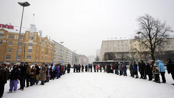 Ihmisiä jonossa lumisateessa.