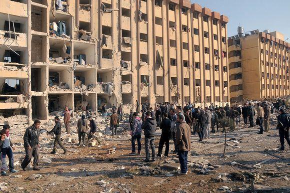 Ihmiset tutkivat pommi-iskun aiheuttamia tuhoja Aleppon yliopiston edustalla.
