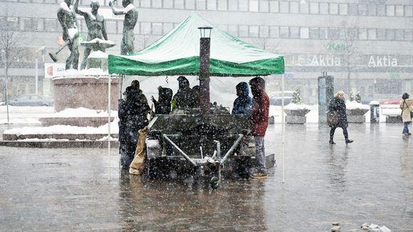 Ihmisä lumisateessa Helsingin Kolmensepänaukiolla helmikuussa.